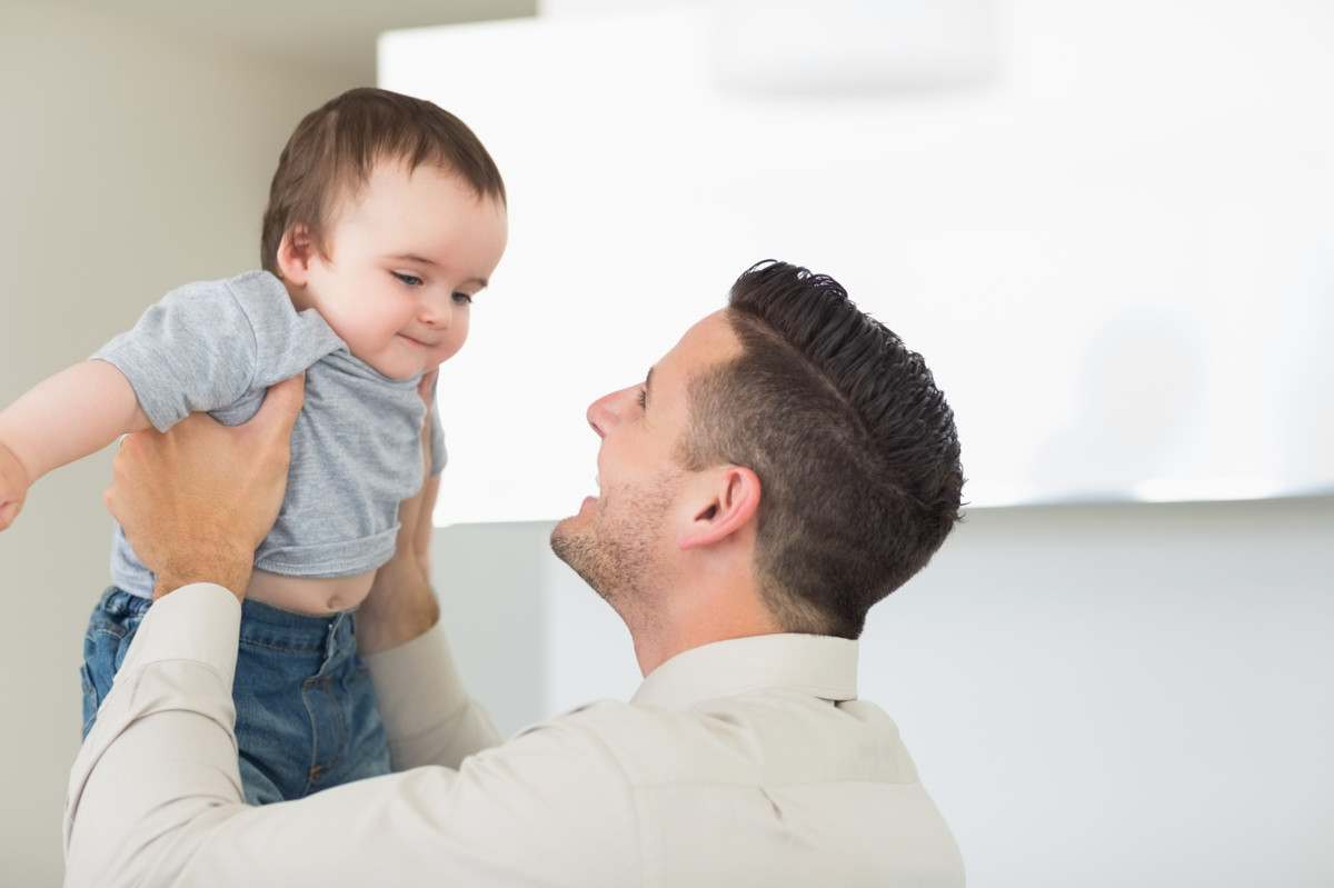 Happy father playing with cute baby boy at home