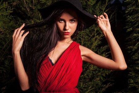 30970952 - beauty brunette women in red dress   hat pose at night park